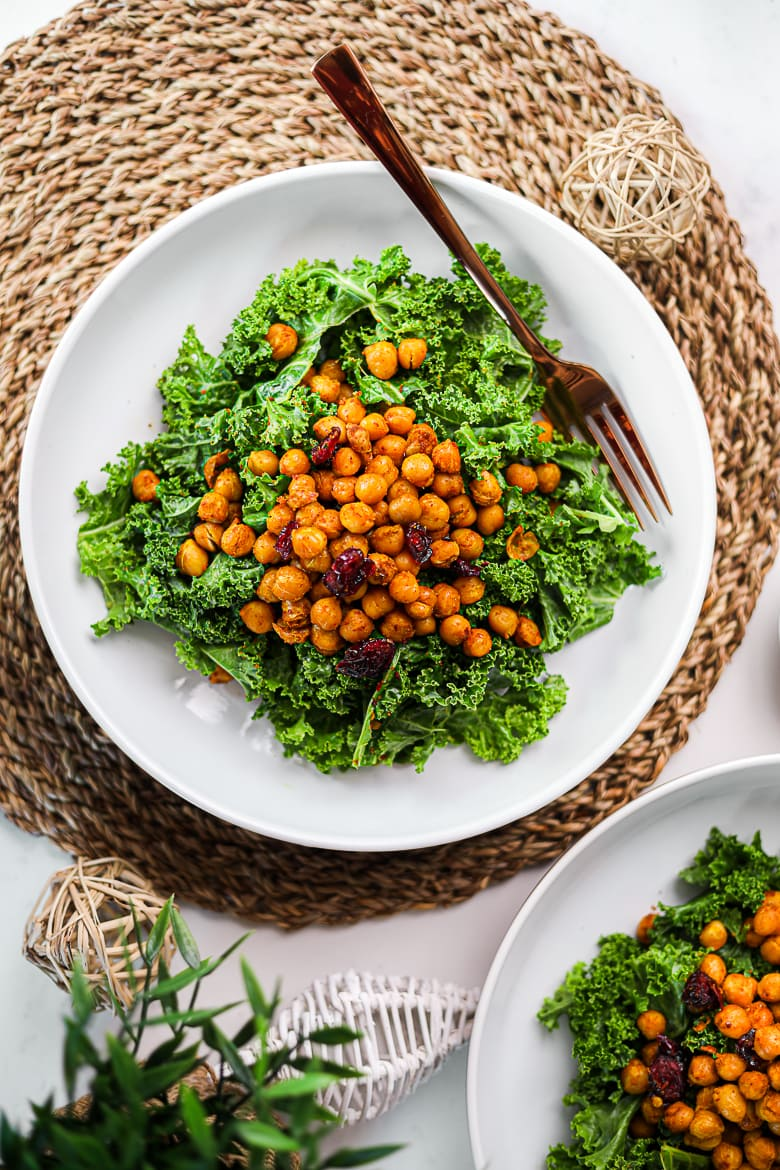flatlay shot of two bowls of kale salad with spicy roasted chickpeas and dried cranberries ontop.