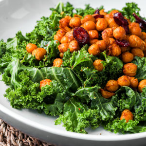 close up of kale salad topped with spicy chickpeas and dried cranberries