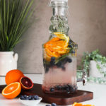 Perspective image of a pitcher containing a water infusion made with orange slices, blueberries, sprigs of rosemary displayed on a wooden board with oranges and blueberries on the side for decoration