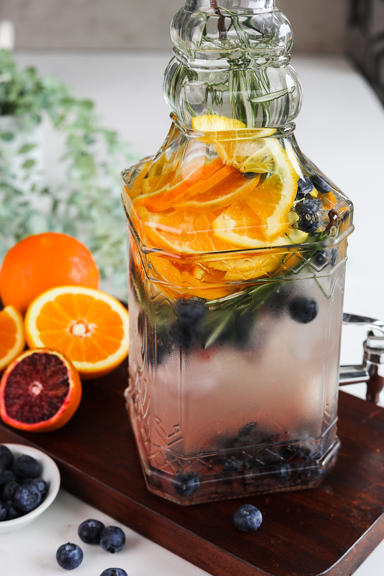 close up angled shot of a pitcher containing a fruit water infusion with orange slices, blueberries and sprigs of rosemary placed on a wooden board
