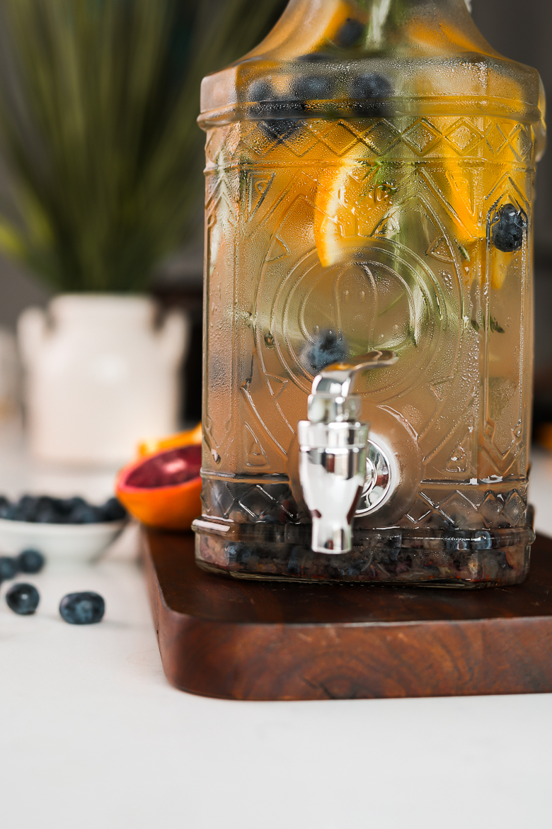 close up image of a pitcher containing a fruit water infusion with orange slices, blueberries and sprigs of rosemary