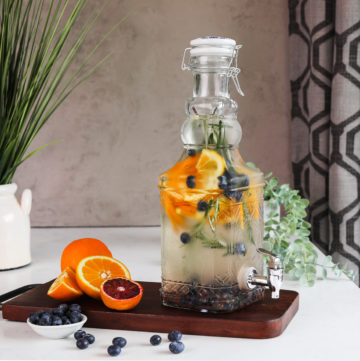 A pitcher containing a blueberry orange water infusion with springs of rosemary, displayed on a wooden board with fresh oranges and blueberries next to it