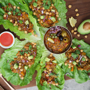 lettuce leaves filled with baingan bharta - an Indian vegetable recipe with a gold bowl in the middle of the leaves.
