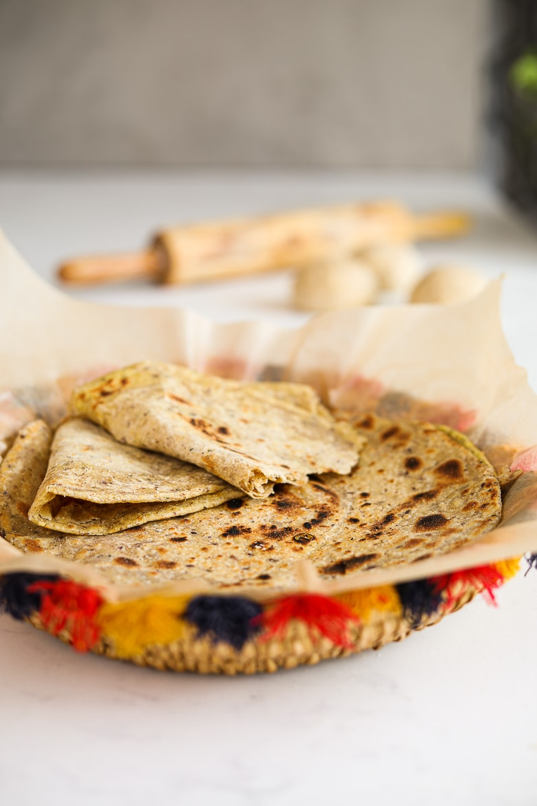 a colourful traditional South Asian straw basket containing a pile of parathas (Indian flat bread) with one paratha ripped in half. A rolling pin and balls of dough in the background