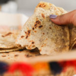 Close-up view of a lady holding half a paratha in a colourful traditional woven basket.