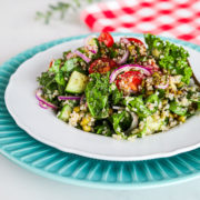 a plate of kale and quinoa salad with tomatoes, red onion and mung beans