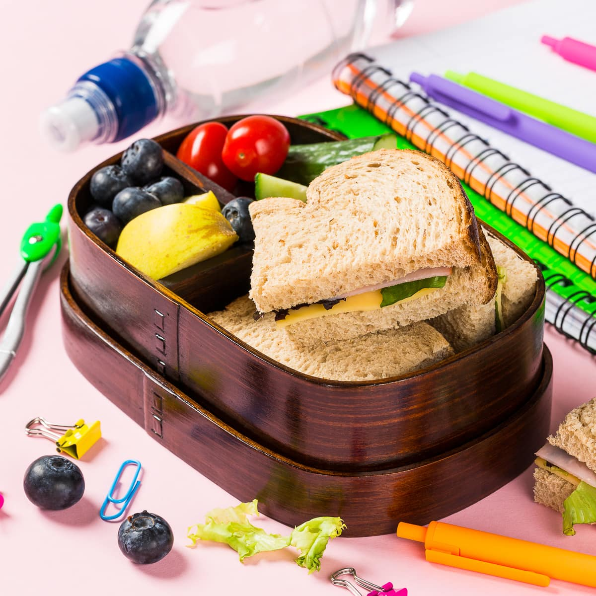 Wooden lunch box with sandwiches, vegetables and fruits on pink background and school stationery. Childrens eating concept.