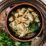 a clay pot with creamy chicken korma garnished with cilantro on a round rustic tray with a bunch of cilantro on the side