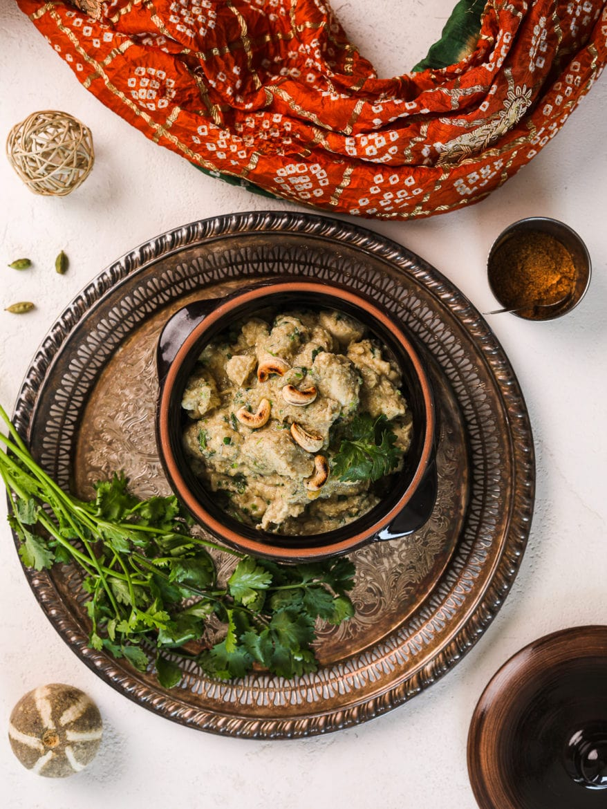 a clay pot with creamy chicken korma garnished with cilantro on a round rustic tray with a bunch of cilantro on the side and a traditional Indian scarf on the side - flatlay