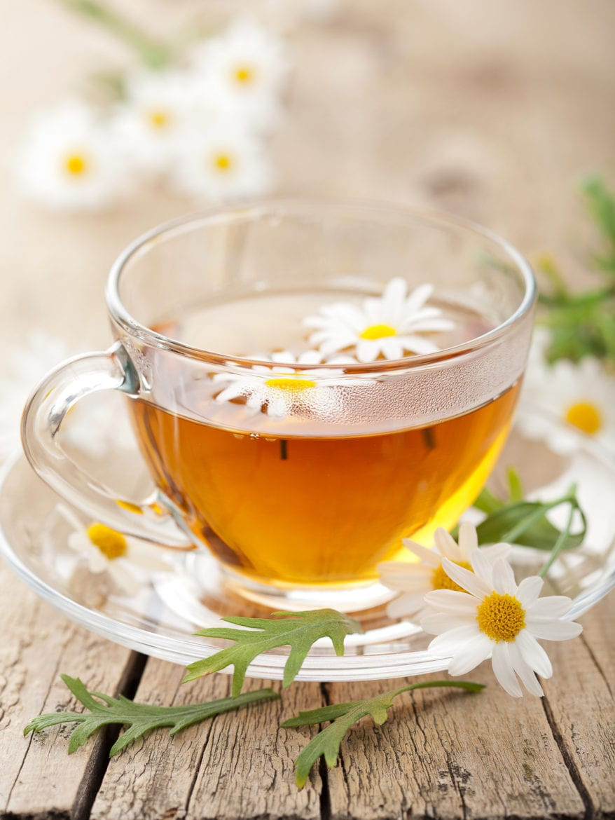 cup of herbal tea with chamomile flowers as a natural way to fall asleep