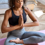 Young adult calm African American woman wearing sportswear sitting at home in bedroom doing yoga exercise, practicing meditation meditating and breathing in the morning. Mental balance concept