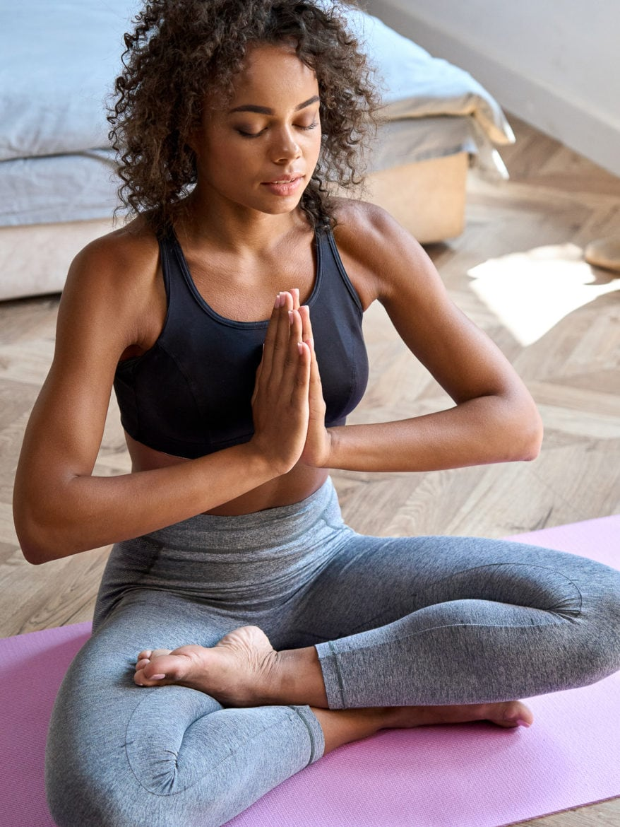 Young adult calm African American woman wearing sportswear sitting at home in bedroom doing yoga exercise, practicing meditation meditating and breathing in the morning. Mental balance concept as natural ways to fall asleep