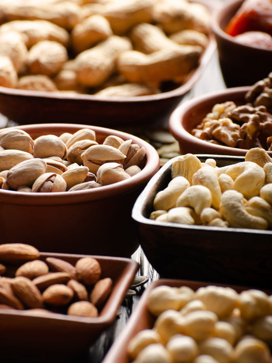 Assorted nuts and seeds in clay bowls on wooden kitchen table