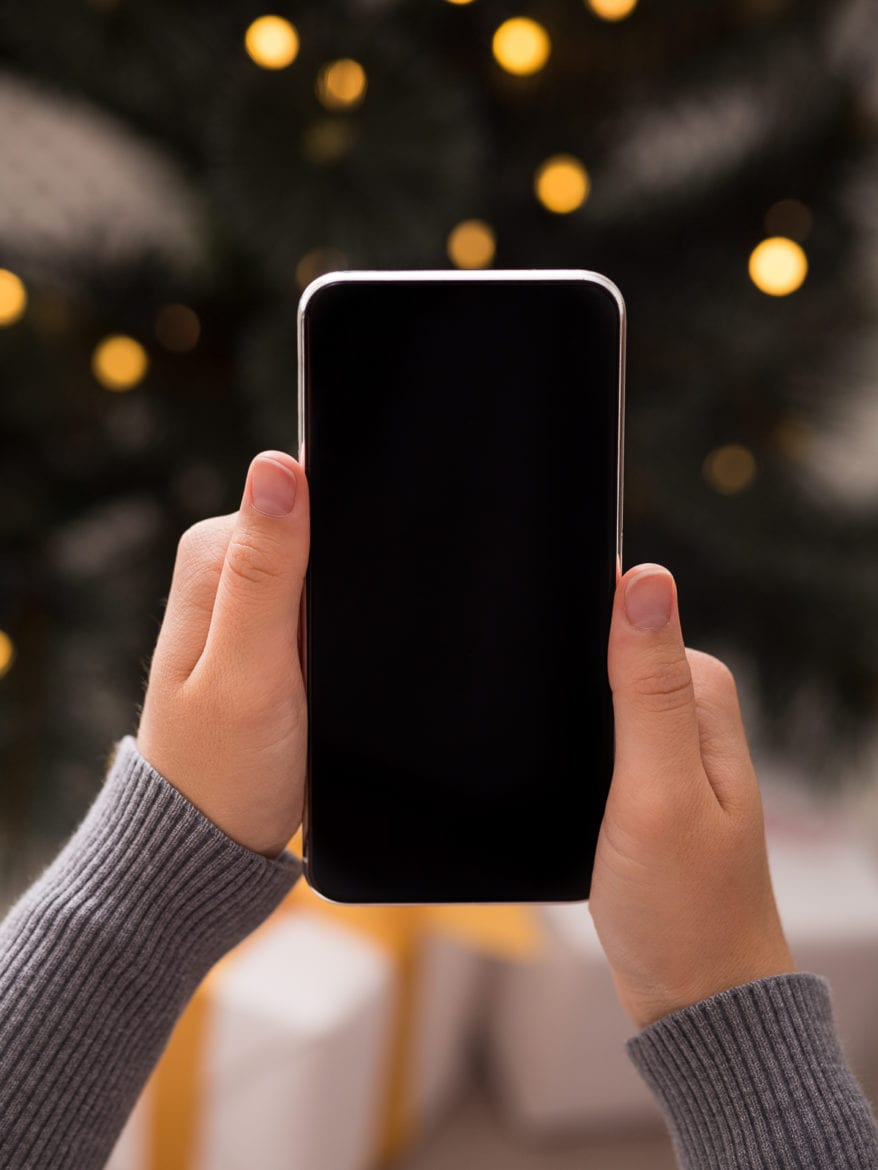 Searching for gifts. Cellphone in woman hands in over background with Christmas tree and presents, blank screen as natural ways to fall asleep
