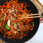 a wok with veg noodles topped with lime slices and sesame seeds - with someone holding a portion of noodles with chopsticks