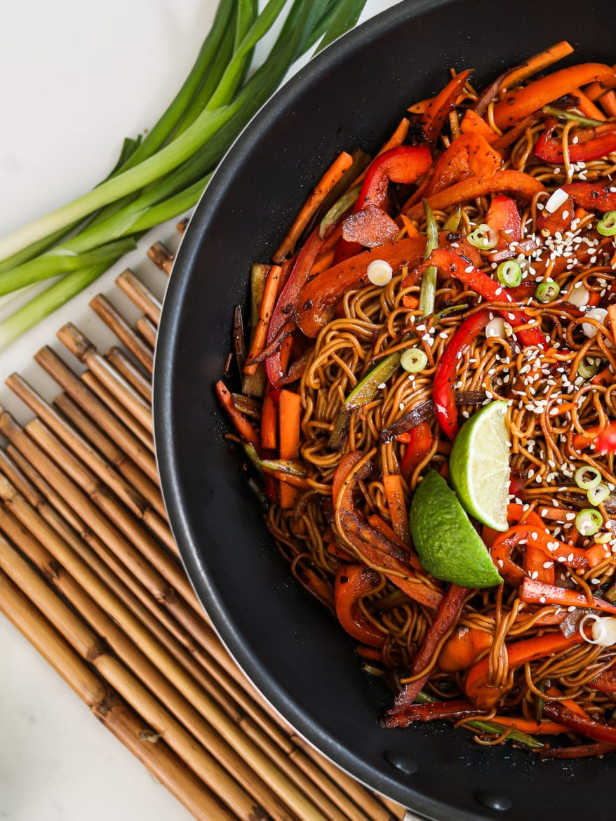image showing half a wok of veg noodles topped with lime wedges