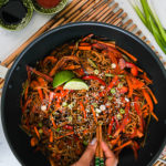 a wok with veg noodles topped with lime slices and sesame seeds - with someone holding a portion of noodles with chopsticks. Wok placed on a bamboo base with spring onions on the side