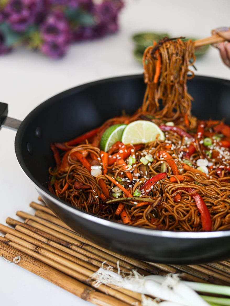 a wok with veg noodles topped with lime slices and sesame seeds - with someone holding a portion of noodles with chopsticks in the background - perspective shot