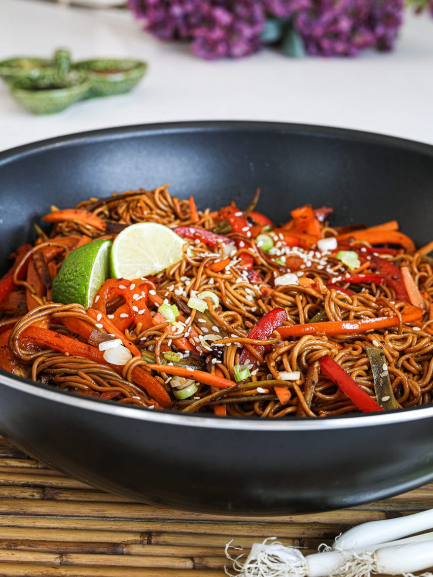 close up image of veg noodles topped with lime wedges with lilac flowers in the background