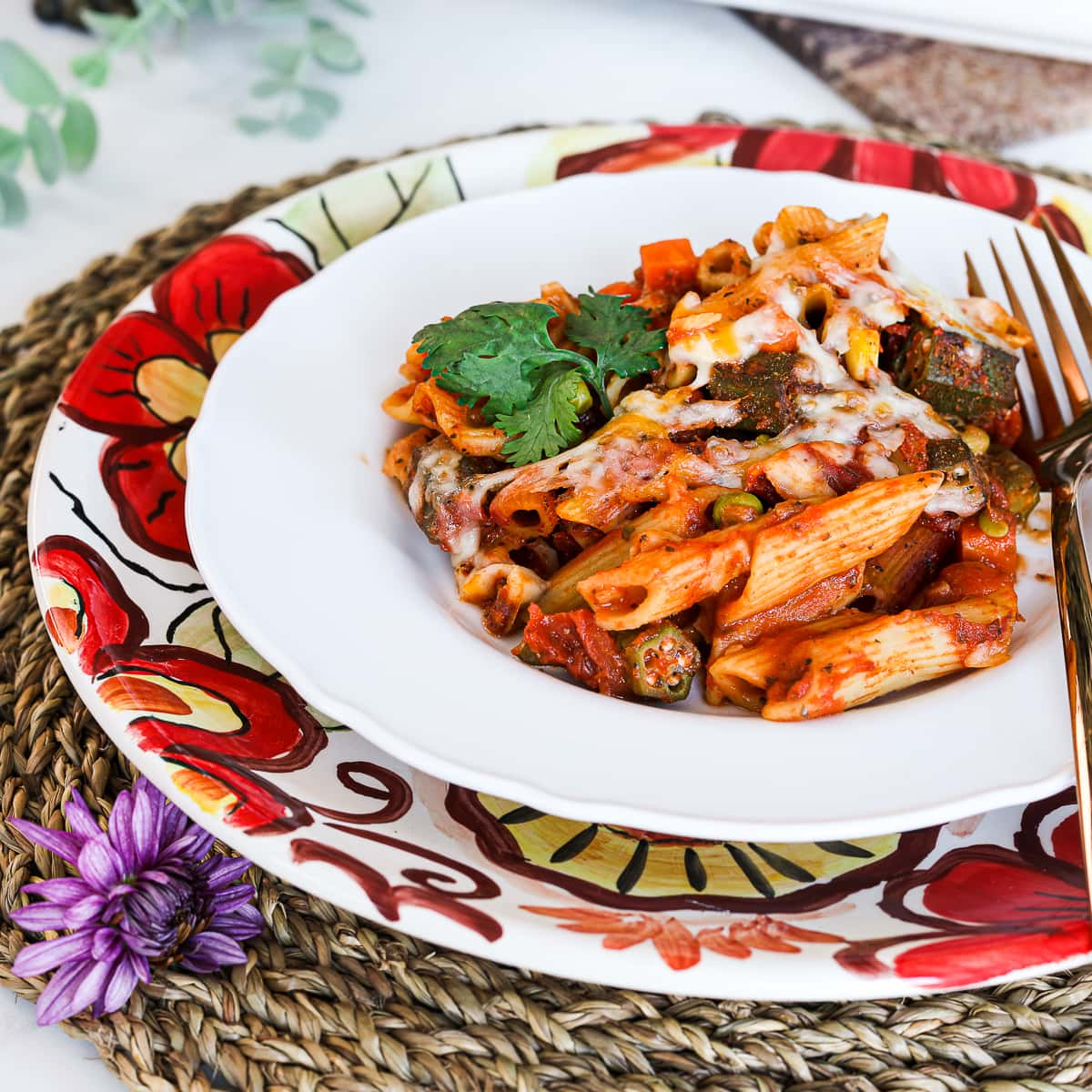 a plate with pasta bake made with penne pasta, okra and mixed vegetables. Garnished with cilantro. Styled on top of a floral plate on a straw mat.