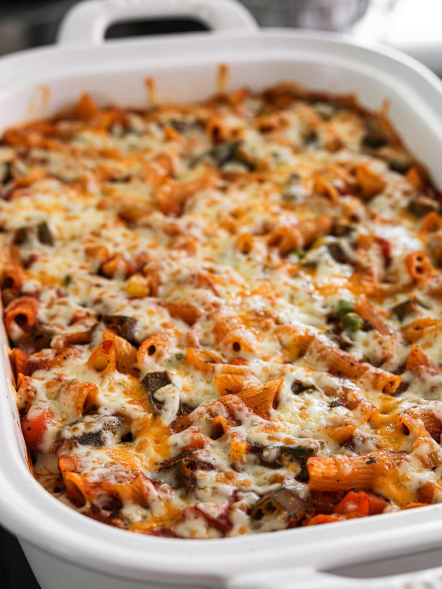 a white rectangular casserole dish with pasta bake made with mixed vegetables topped with melted cheese on - close up shot