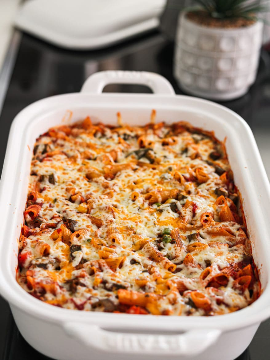 a white rectangular casserole dish with pasta bake topped with melted cheese on a black stovetop with a green plant in the background
