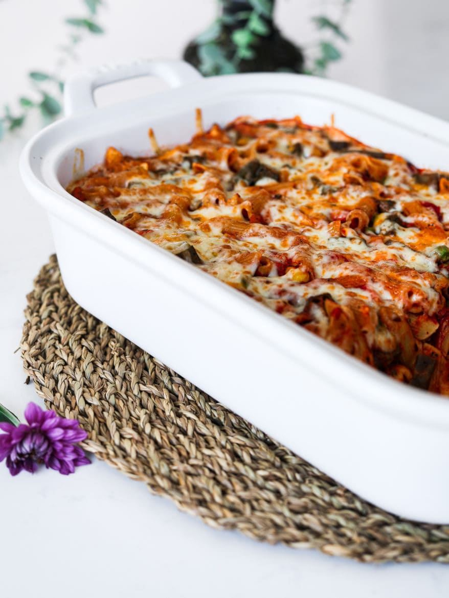 a white rectangular casserole dish with pasta bake topped with melted cheese on a brown straw mat with a green plant in the background