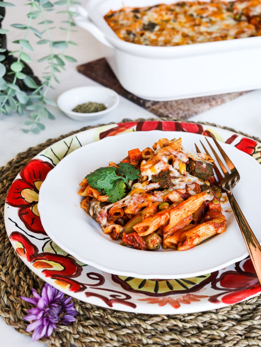 a plate with pasta bake made with penne pasta, okra and mixed vegetables. Garnished with cilantro. Styled on top of a floral plate on a straw mat with a casserole dish in the background and a green plant