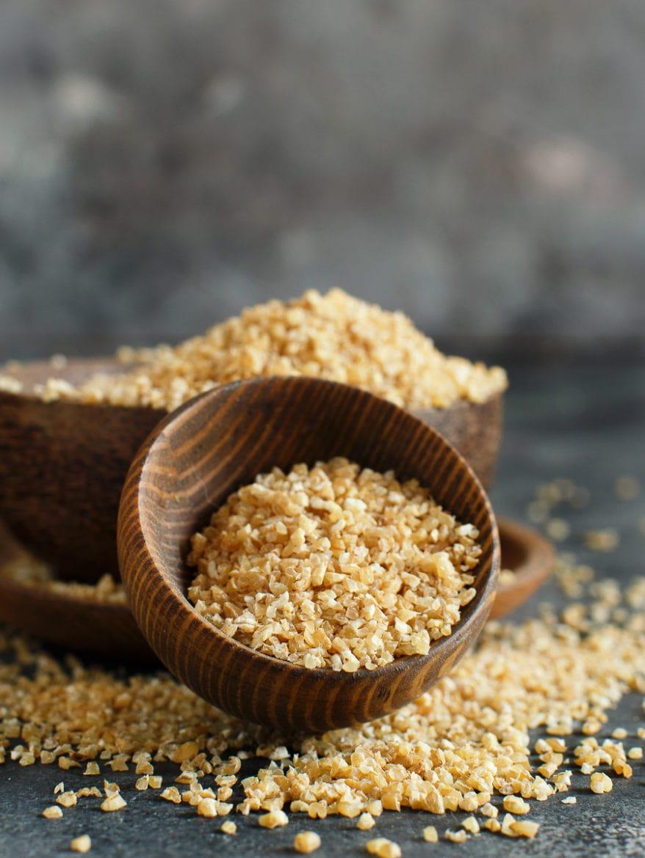Dry bulgur wheat grains in bowls close up