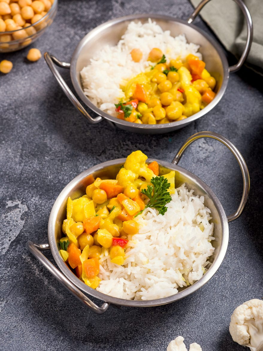 Vegetarian curry with cauliflower and chickpeas served in metal bowls with rice, healthy vegan food, indian cuisine