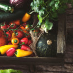 Organic vegetables on wood.Harvested vegetables. Rustic setting with pumpkins, peppers, tomatoes and lettuce