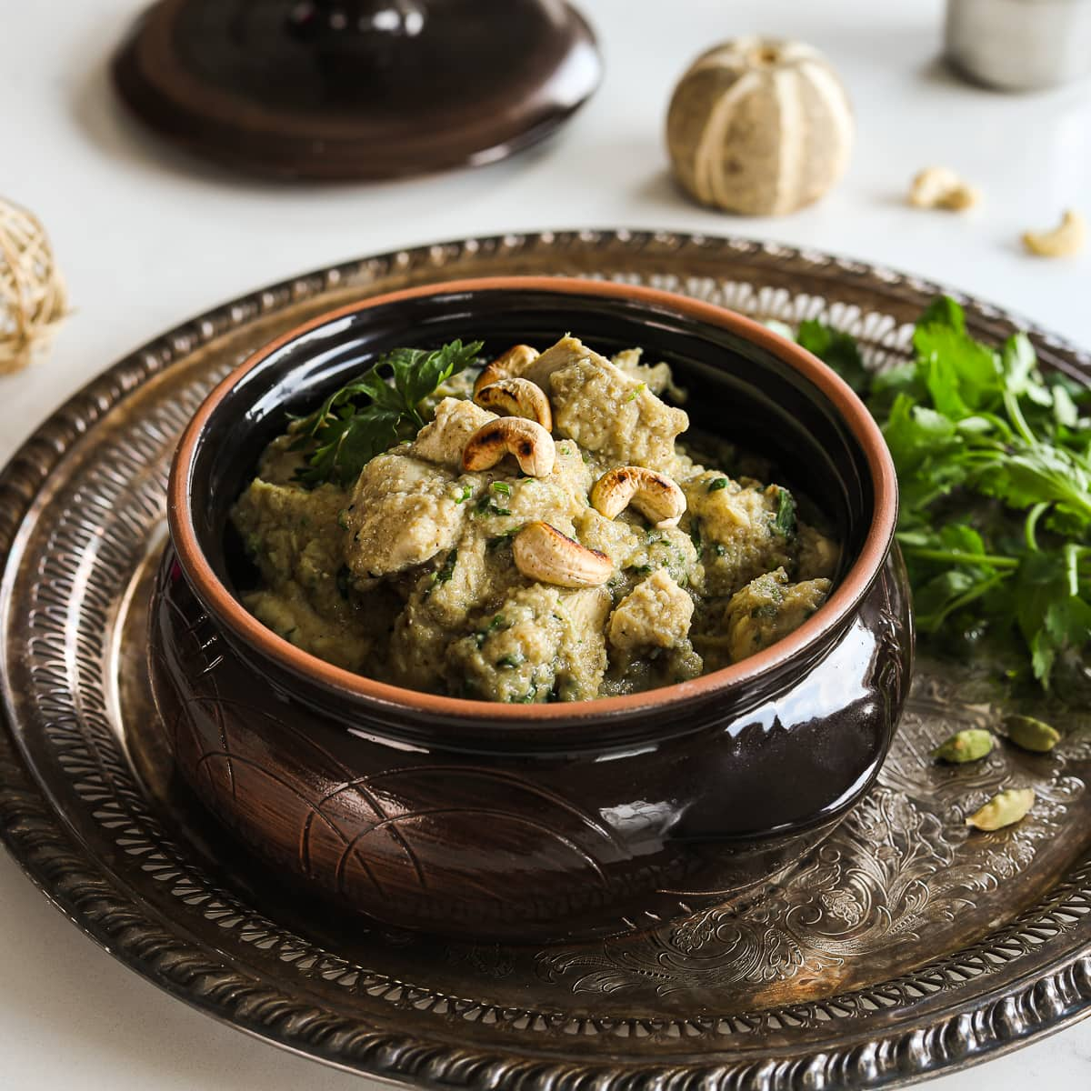 a clay pot with creamy chicken korma garnished with cilantro and topped with cashews on a round rustic tray with a bunch of cilantro on the side