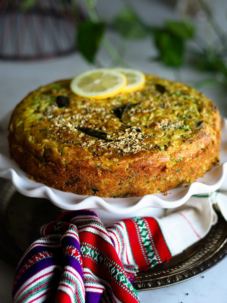 An orange coloured cake on a cake stand placed on a tray with a traditional Indian shawl - topped with 2 lemon slices