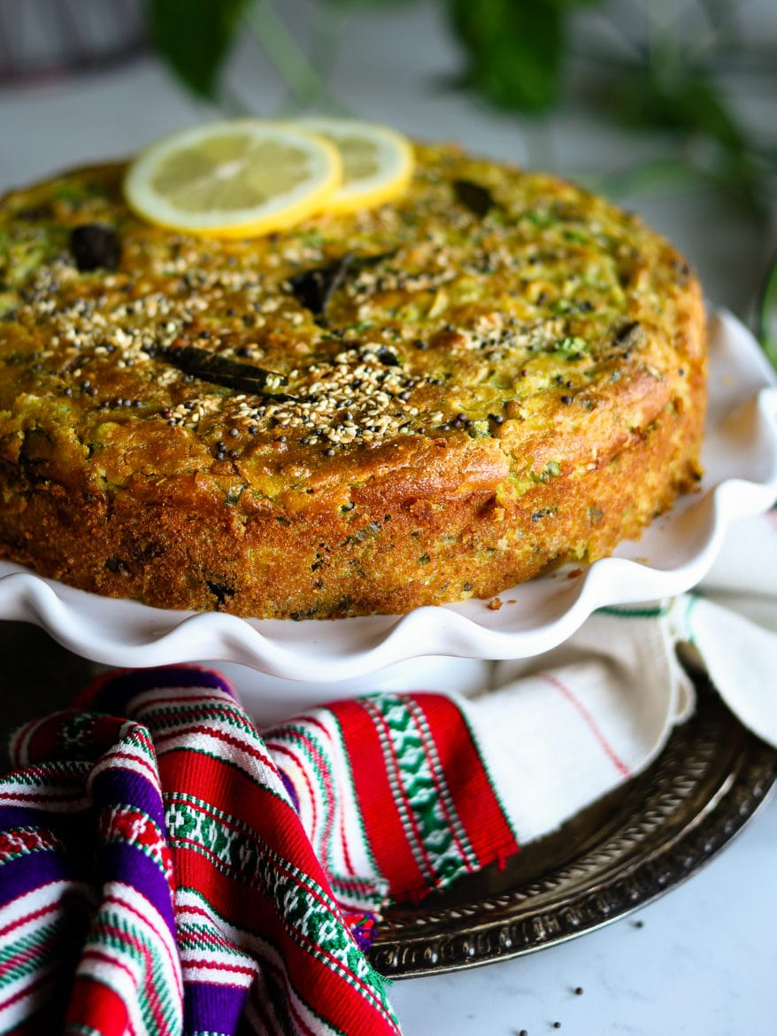 An orange coloured cake on a cake stand placed on a tray with a traditional Indian shawl