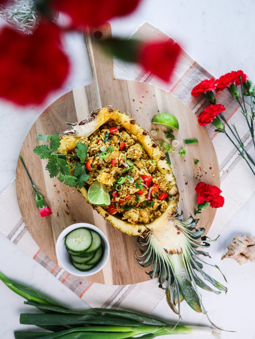 half a pineapple stuffed with Thai pineapple fried rice topped with a lime segment and cilantro on a round wooden board decorated with red flowers arranged around.