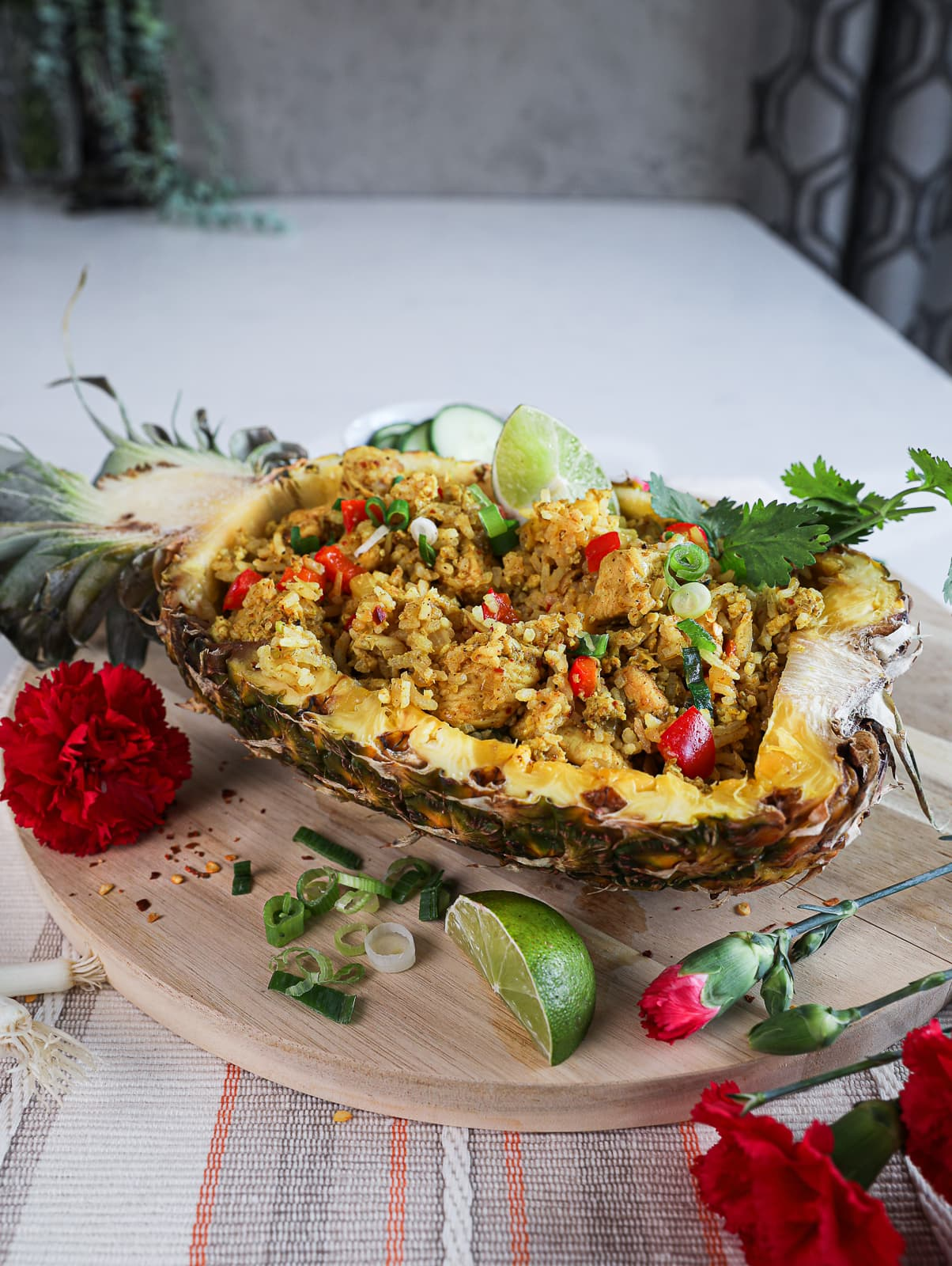 side shot of half a pineapple stuffed with Thai pineapple fried rice topped with cilantro on a round wooden board decorated with red flowers arranged around.