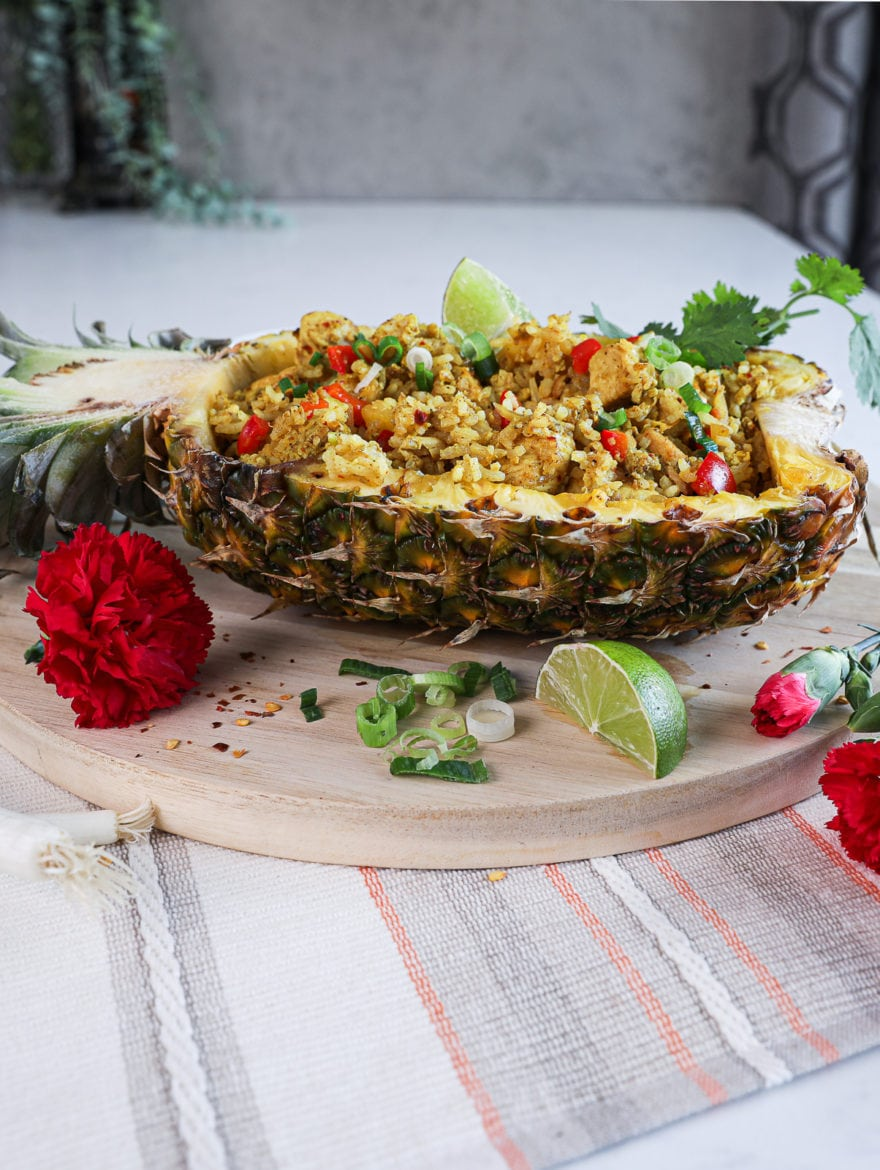 side shot of half a pineapple stuffed with Thai pineapple fried rice topped with a lime segment and cilantro on a round wooden board decorated with red flowers arranged around.