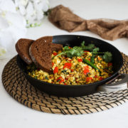 fry pan of vegan tofu scramble with red pepper cubes topped with cilantro and green chilli and two slices of pumpernickel bread placed on top