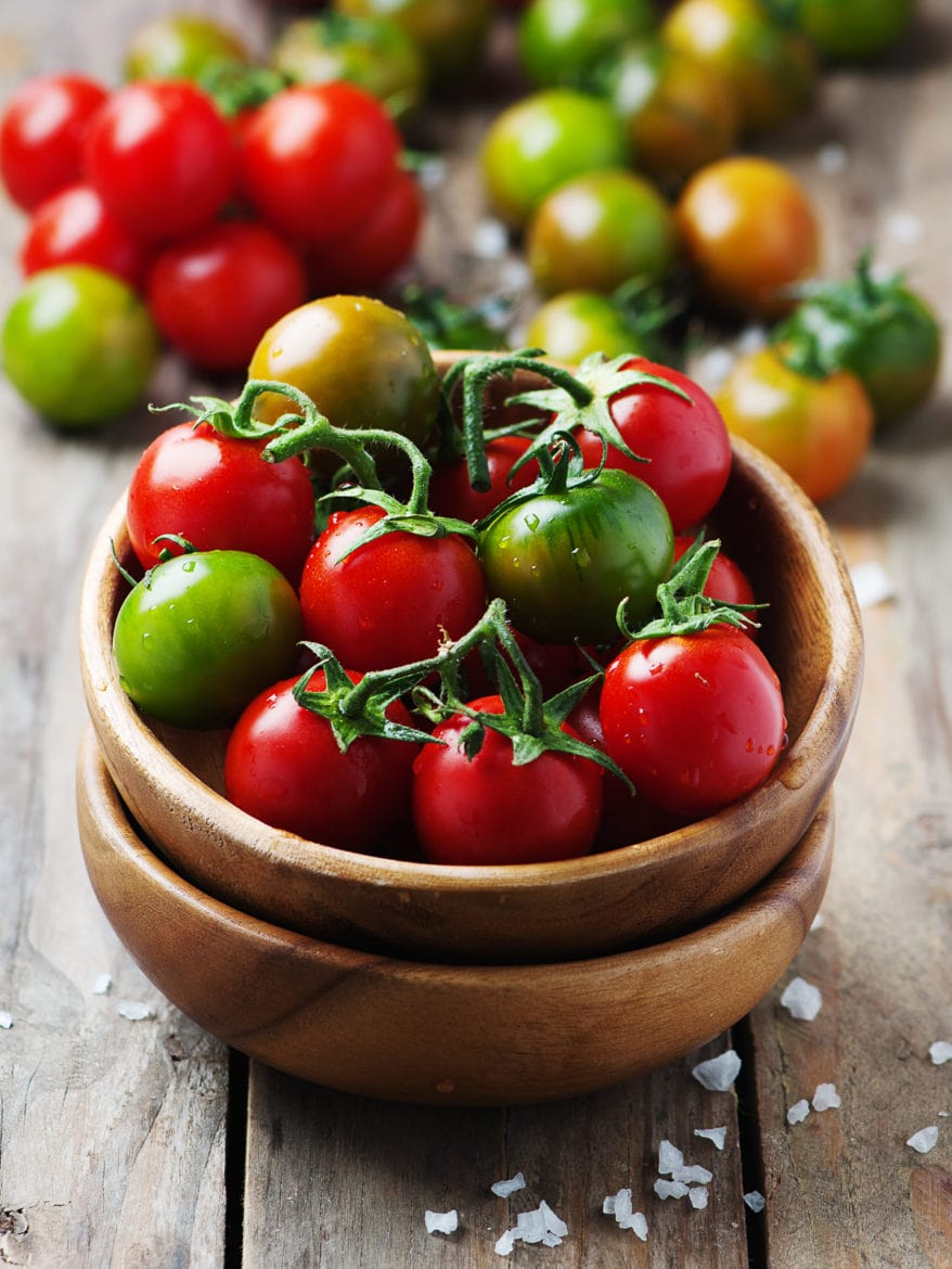 Concept of vegan food, selective focus colourful tomatoes in a wooden bowl