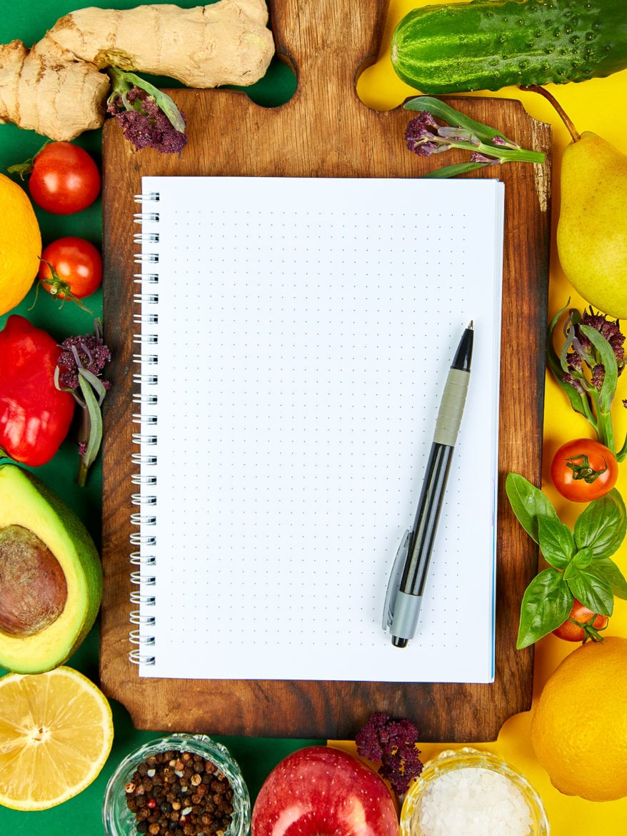 Shopping list, recipe book, diet plan. Fresh raw vegetables, fruit and ingredients for healthy cooking. top view, place for text. Diet or vegan food, vegetarian and healthily cooking concept. Flat lay. Notepad for your recipe concept.