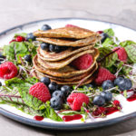 Vegan chickpea pancakes served in plate with green salad young beetroot leaves, sprouts, berries, berry sauce over grey kitchen table. Close up. Healthy eating