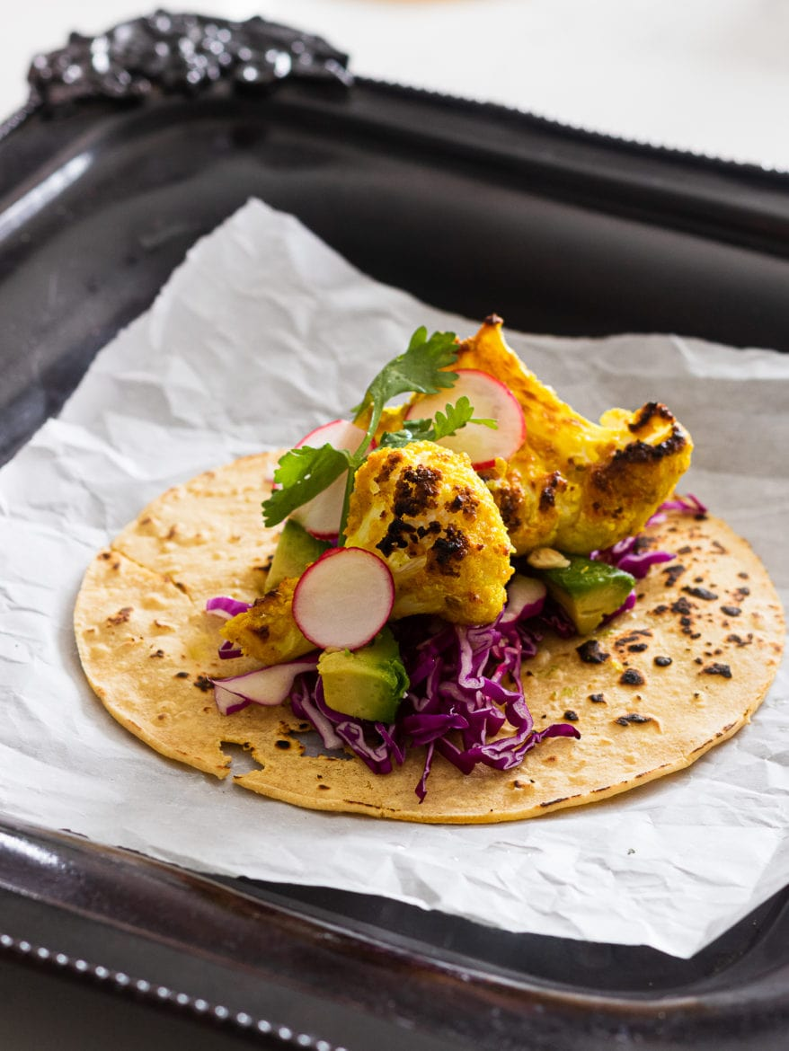 tandoori cauliflower florets on a corn tortilla with red cabbage and herbs