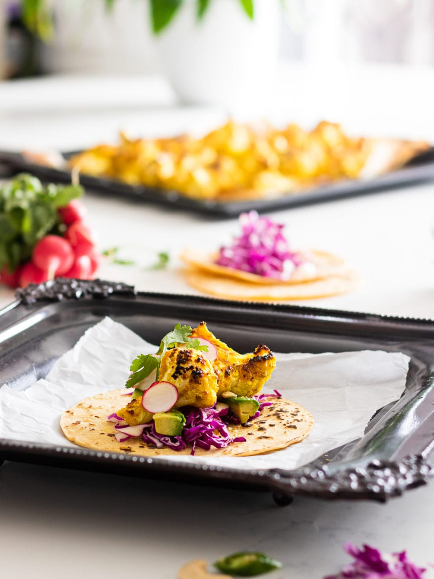 Tray with a corn cauliflower taco and purple cabbage and avocado cubes