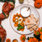 Kadoo (Afghan Pumpkin Curry) presented on a white plate alongside a small bowl of yoghurt and pita bread on a white background with a traditional scarf, small pumpkins and orange flowers all around.