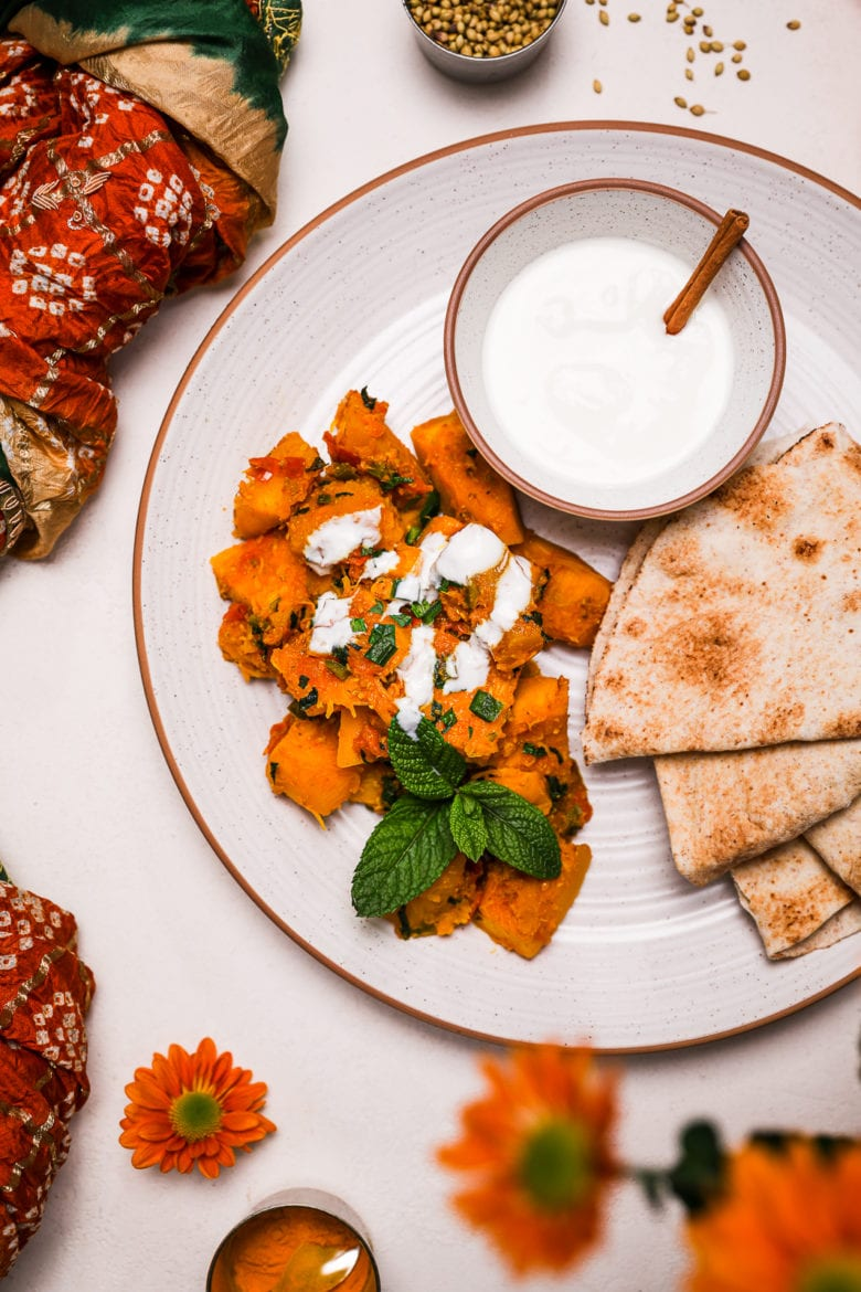 Kadoo (Afghan Pumpkin Curry) presented on a white plate alongside a small bowl of yoghurt and pita bread on a white background with flowers and spices pots close by