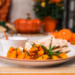 Kadoo (Afghan Pumpkin Curry) presented on a white plate alongside a small bowl of yoghurt and pita bread on a white background with two small aluminium bowls and a pumpkin shaped cocotte with a few orange flowers in the foreground