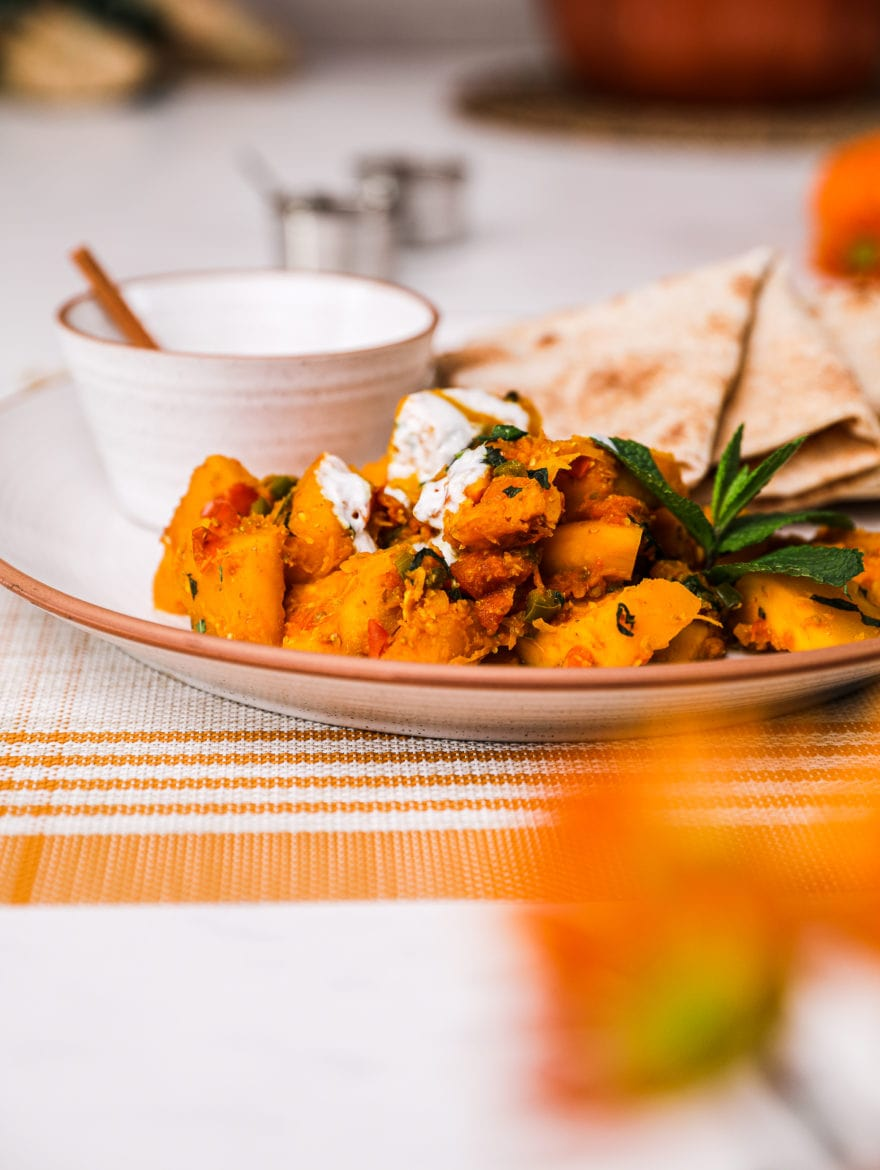 Kadoo (Afghan Pumpkin Curry) presented on a white plate alongside a small bowl of yoghurt and pita bread on a white background with two small aluminium bowls and few orange flowers in the foreground